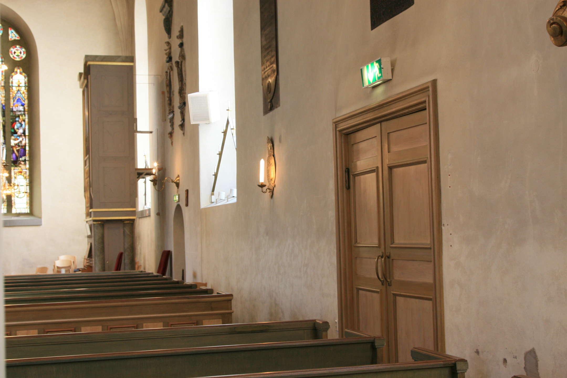 Södra långväggen med en kyrkhögtalare i fönstret.